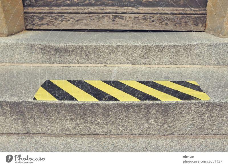 gelb-schwarzer Signalstreifen als Abstandshalter auf einer Treppenstufe vor einer alten Holztür Schutzmaßnahme Kontaktsperre Infektionsschutz Corona