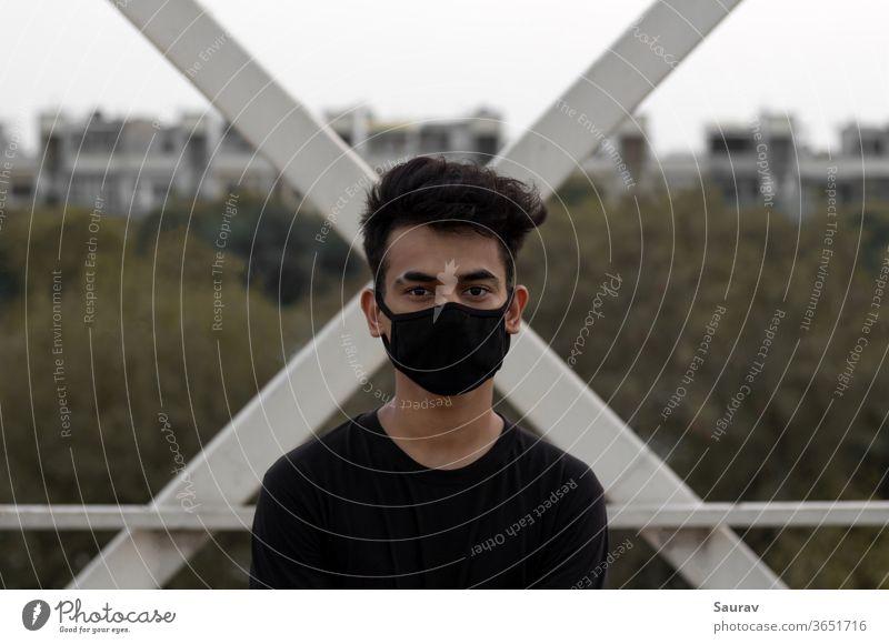 Ein junger Mann trägt eine schützende Gesichtsmaske, um eine Coronavirus-Infektion in einer Stadt zu vermeiden. Bund 19 junger Erwachsener Mundschutz Großstadt