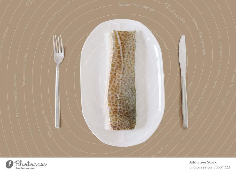 Rohes Kabeljaufilet auf dem Tisch Fisch Filet roh Asiatische Küche Meeresfrüchte Protein Dorsch Gesundheit Messer Gabel Speise Tradition Keramik Teller Haut