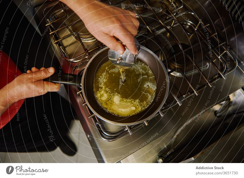 Ernte unkenntlich Koch gießt Olivenöl in die Pfanne Küchenchef eingießen Erdöl oliv zerlaufen Butter braten Herd kulinarisch Prozess vorbereiten Lebensmittel