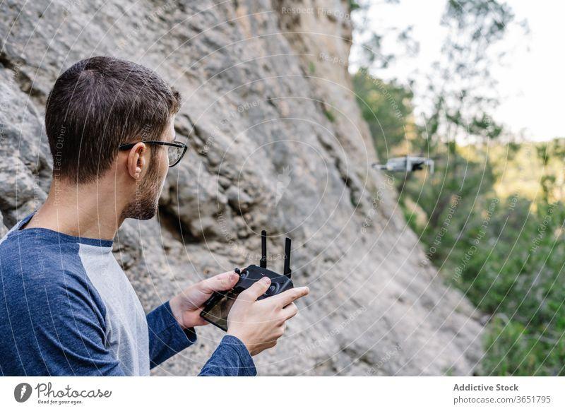 Fokussierter Mann steuert Drohne aus der Ferne Kontrolle Dröhnen Fliege abgelegen arbeiten Quadrokopter Regler Gerät unbemannt Flug männlich Landschaft
