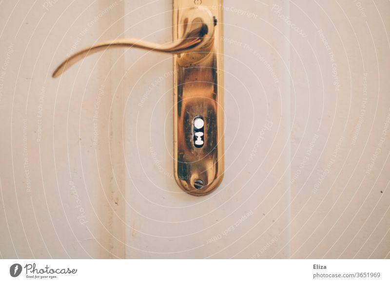 Weiße Tür mit altmodischen Türschloss und Türklinke in gold Schloss Schlüsselloch verschnörkelt Griff Sicherheit Eingang Eingangstür Holz weiß vintage Holztür