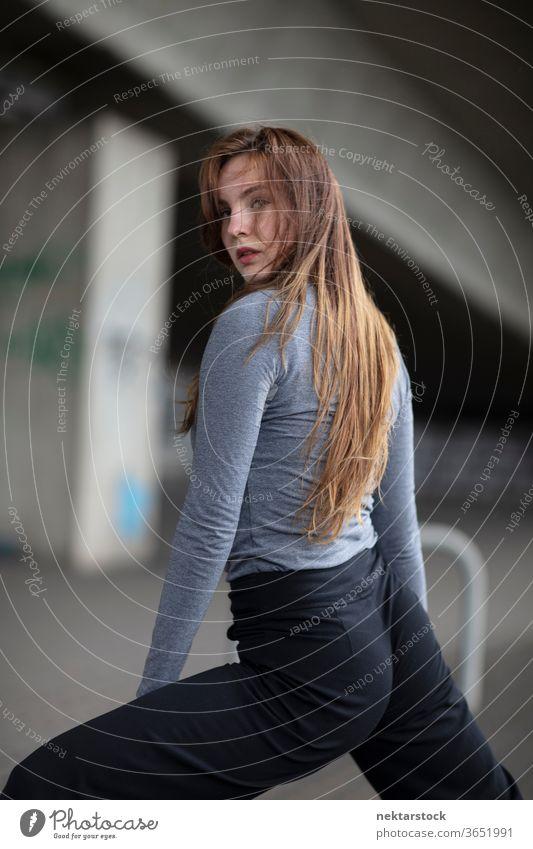 Rückansicht einer Tänzerin, die in Tanzpose in die Kamera schaut Frau Pose Model verführerisch Tanzstand Selektiver Fokus Haare im Gesicht in die Kamera schauen