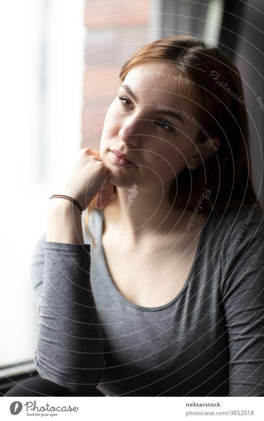 Schönes Porträt einer jungen Frau am Fenster sitzend mit der Hand auf dem Kinn eine Person Mädchen Junge Frau Hand am Kinn posierend im Innenbereich Pose