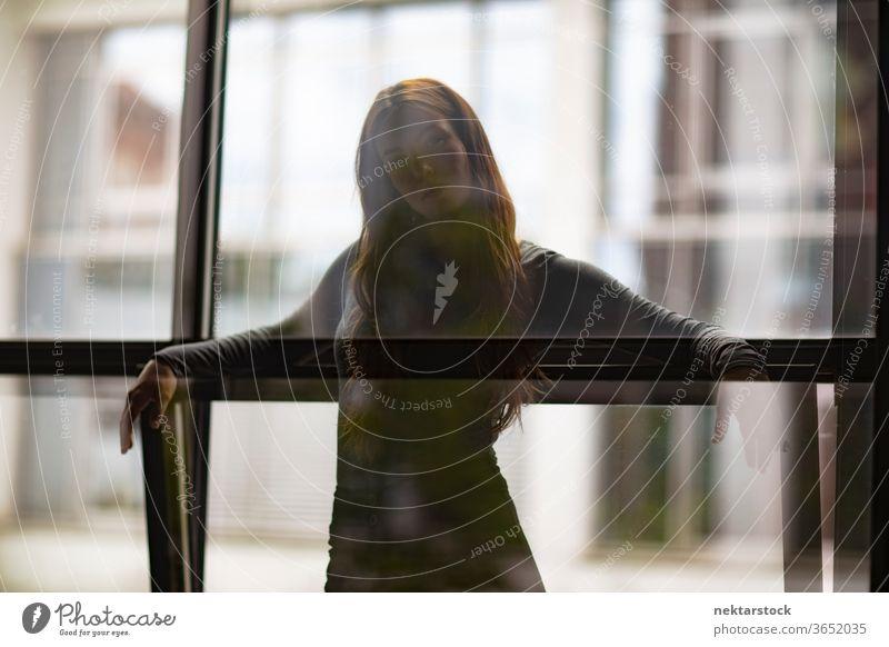 Attraktive Frau hinter Fenster Glastrennwand eine Person Mädchen Junge Frau Silhouette Dreiviertellänge Kontemplation Gedanke in die Kamera schauen