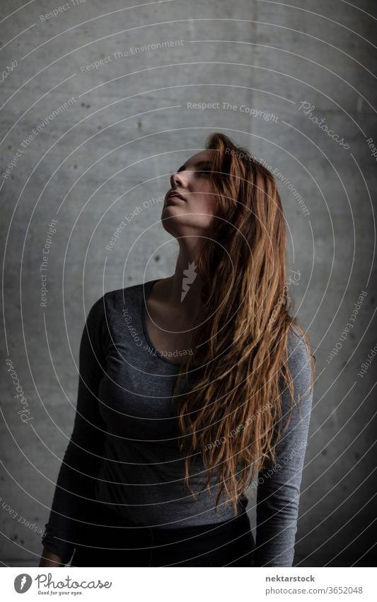 Junge Frau mit erhobenem Kinn blickt nach oben eine Person Mädchen Frisur Porträt aufschauend Kopf erhoben kaukasische Ethnizität Jugendkultur Beton brünett