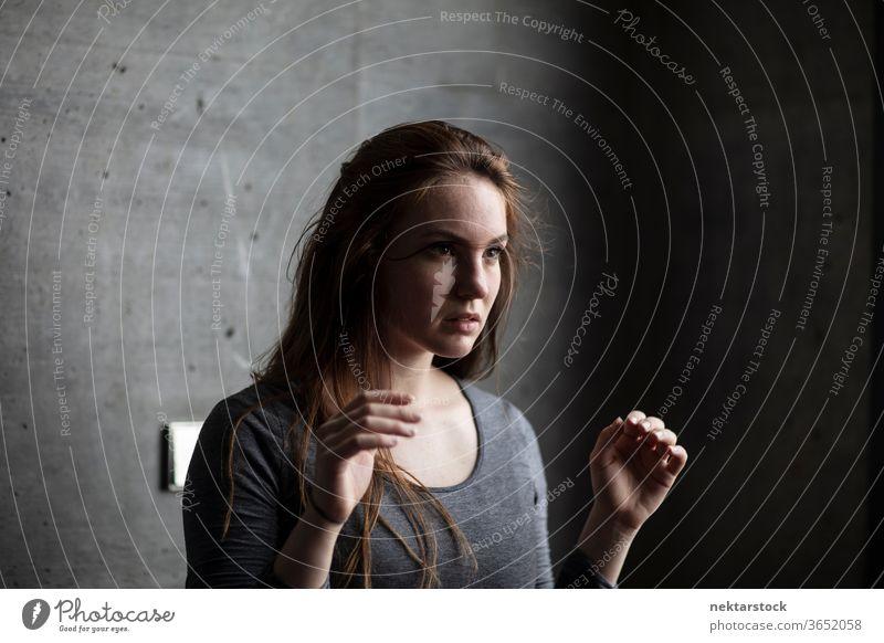 Junge Frau hebt die Arme hinter grauer Betonmauer eine Person Mädchen Porträt Frisur kaukasische Ethnizität Jugendkultur brünett lange Haare Hände Hände hoch
