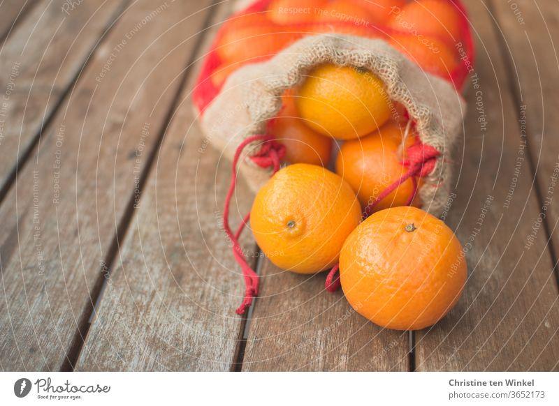 Ein geöffneter Beutel mit Mandarinen liegt auf einem älteren Holztisch. Zwei Früchte liegen vor dem Beutel. Nahaufnahme mit schwacher Tiefenschärfe