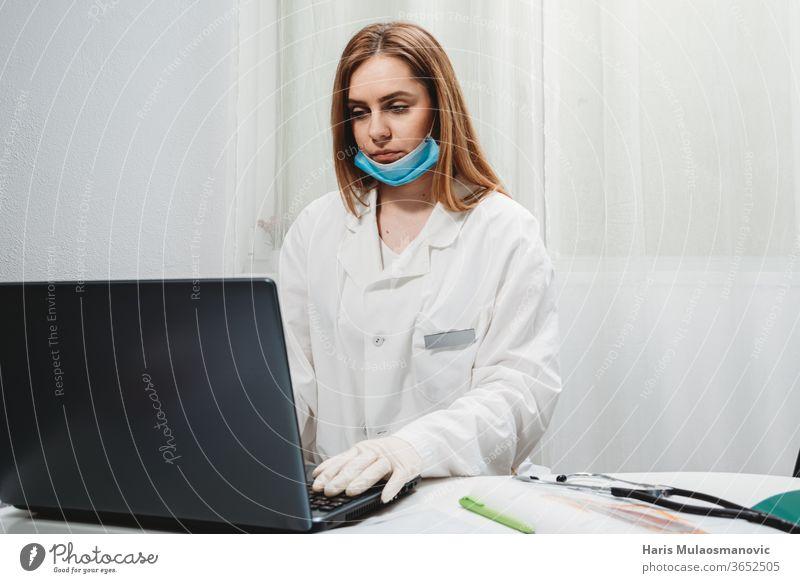 Ärztin mit Maske arbeitet am Laptop in der Arztpraxis 2020 Atemschutzmaske schwarzer Hintergrund Klinik Korona-Epidemie Corona-Virus covid-19 covid-19-Test