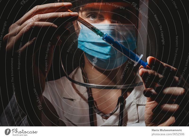 Ärztin mit Maske und Schild, die den Impfstoff in den Händen hält, auf schwarzem Hintergrund 2020 Atemschutzmaske schwarzer Hintergrund Klinik Korona-Epidemie