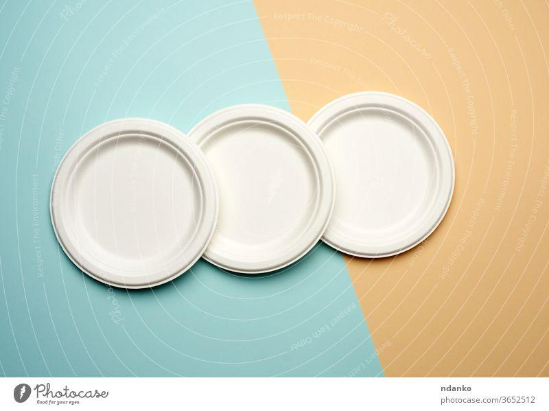 Stapel weißer Papier-Einwegteller auf beige-blauem Hintergrund, Draufsicht Picknick Teller wiederverwerten Restaurant Atelier Geschirr Vorlage dick Top Utensil