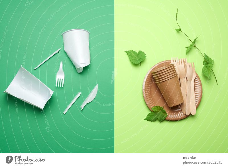 nicht abbaubarer Kunststoffabfall von Einweggeschirr und einem Geschirrset aus umweltfreundlichen recycelten Materialien auf grünem Hintergrund Widerspruch