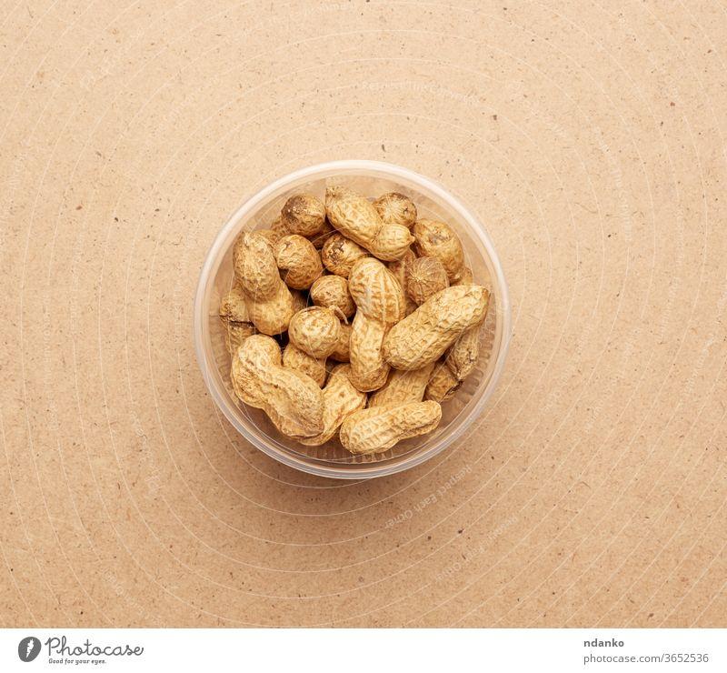 Inshell-Erdnüsse in einer durchsichtigen Plastikschale Nut Nährstoff Ernährung Nussschale offen organisch Erdnuss sich[Akk] schälen Haufen Hülse roh Samen