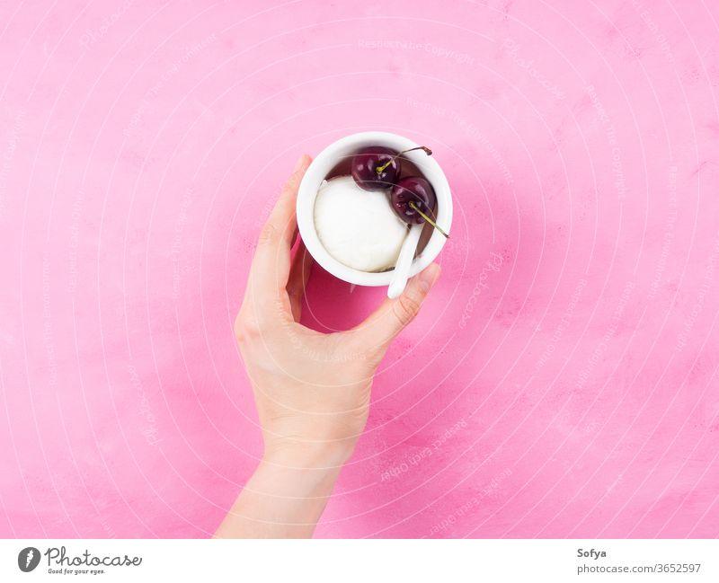 Gefrorenes Joghurt-Dessert im Becher in Frauenhand Baggerlöffel Sorbet Hand Beteiligung gelato Speiseeis rosa Kirsche sehr wenige gefroren weiß Beeren Eisbecher