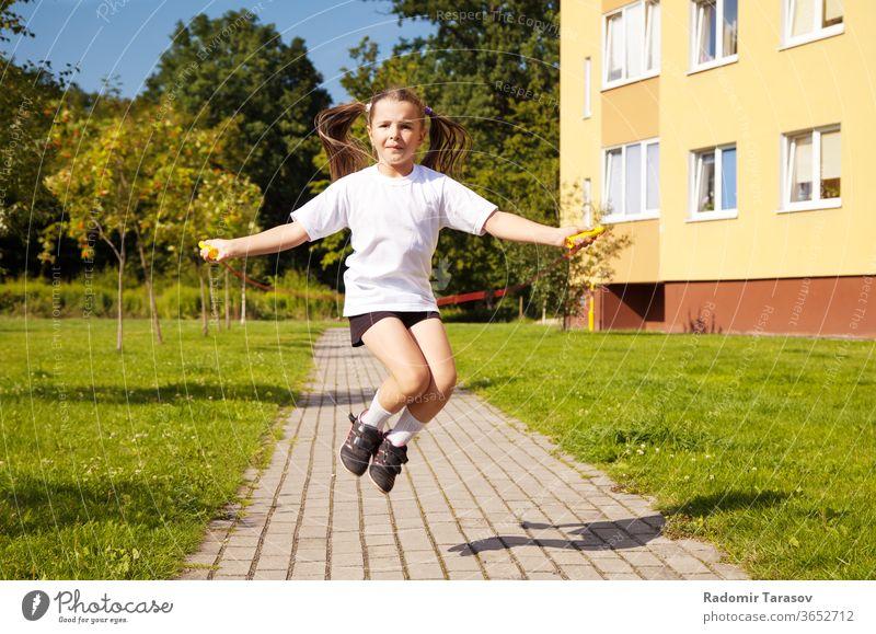 kleines Mädchen springt Seil nach draussen springen Kind niedlich schön wenig weiß Spaß hübsch heiter Lifestyle Kindheit spielen Menschen Kaukasier Freude