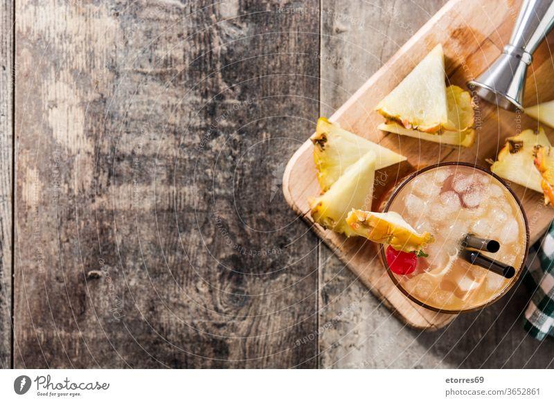 Kalter Mai-Tai-Cocktail mit Ananas und Kirsche auf Holztisch. Ansicht von oben. Raum kopieren alkoholisch Getränk Schnaps kalt lecker trinken Lebensmittel