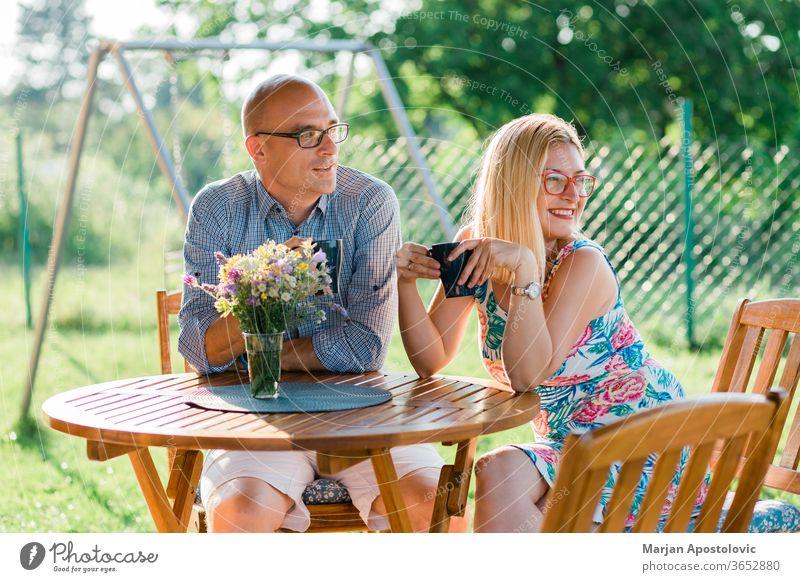 Junges Paar trinkt morgens Kaffee im Hinterhof Erwachsener lässig Kaukasier heiter Mitteilung Land Tag trinken genießend Abend Familie Frau Garten Mädchen
