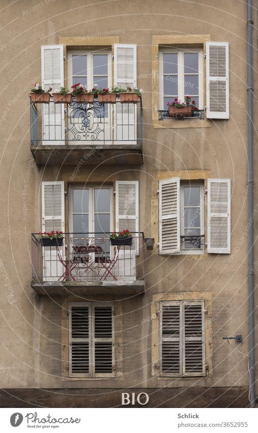 Fassade eines Wohnhauses über einem Bioladen in Metz Lothringen alt Balkone Klappläden Holz Regenfallrohr Fenster Text Haus außen Wohnungen Altbau