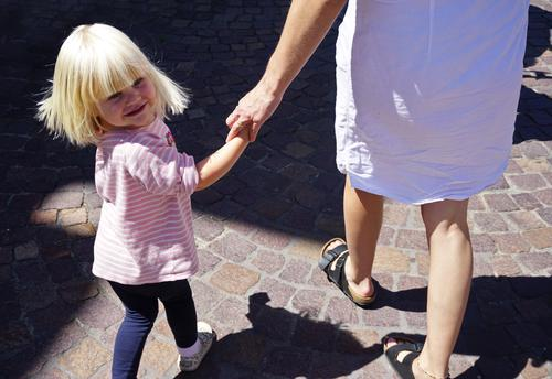 Kleines Mädchen läuft an der Hand ihrer Mutter und schaut mit einem Schwung in den Haaren lächelnd zurück. Kind Elternteil mit Kind laufen Spaziergang Lächeln