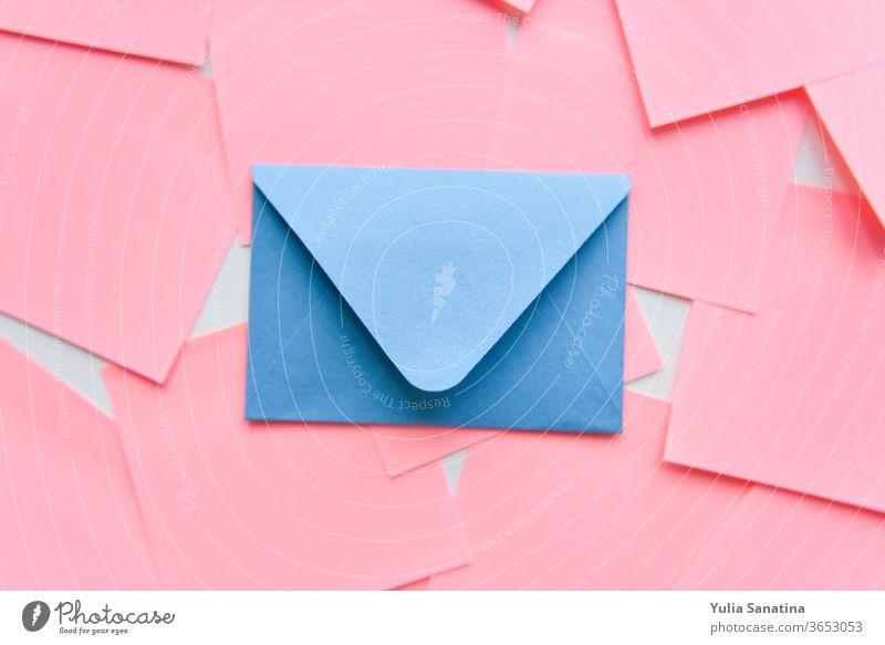 selektiver Fokus, blauer Umschlag auf dem Hintergrund von Korallenaufklebern rosa Kuvert Design Postkarte Liebe Brief vereinzelt Kulisse Hochzeit Papier Kunst