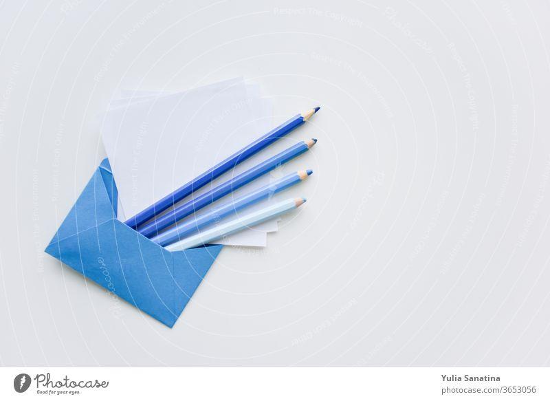 selektiver Fokus, blaue Stifte und weißes Papier aus dem blauen Umschlag mit Kopierraum oben Kuvert Bleistift Schot Hintergrund Nachricht blanko Brief Büro leer