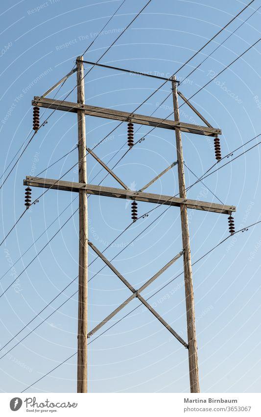 Elektrischer Holzmast mit blauem Himmel im Hintergrund ländlich Spannung Technik & Technologie Elektrizität elektrisch Kraft Industrie Linie Licht Draht Kabel