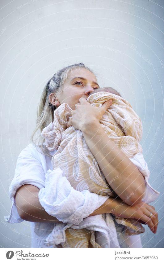 Mutter hält ihr neugeborenes Kind in den Armen und schaut in die Ferne. Junge Frau Liebe Baby Mutterschaft Glück halten festhalten klein Familie beige weiß hell