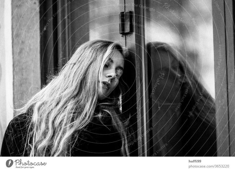 die junge Frau lehnt sich verträumt melancholisch an eine Fensterscheibe Junge Frau Porträt Frauenaugen Frauengesicht Jugendliche Mensch Erwachsene 18-30 Jahre