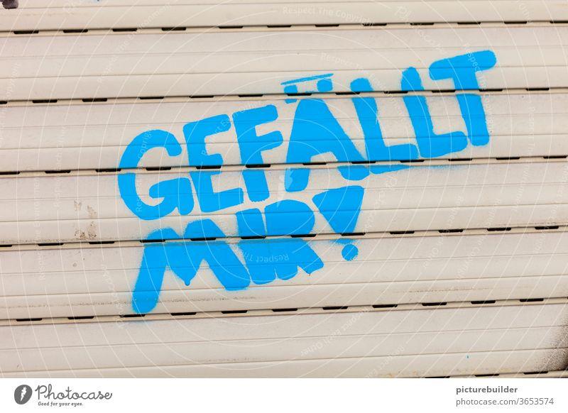Rolladen mit Botschaft  gefällt mir Gefällt mir Graffiti blau beige Fenster geschlossen Außenaufnahme Schriftzeichen Farbfoto Menschenleer Tag erfreut positiv