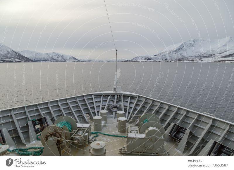 Schiffsbug mit Sicht auf die Lofoten in Norwegen Schifffahrt Meer Nordmeer Skandinavien Winter Berge Schnee Himmel Wolken Bedeckt Kalt Reise Urlaub Seil Winde