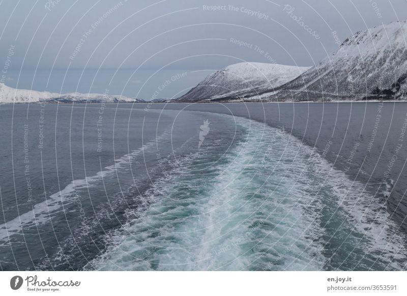 Schifffahrt zu den Lofoten in Norwegen mit Blick auf das Kielwasser Spur Schiffsspur Wasser Meer Nordmeer Skandinavien Winter kalt Schnee Berge grau blau Urlaub