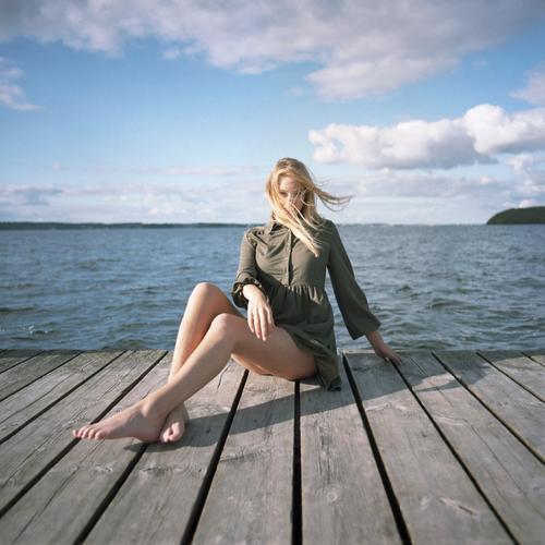 analoges Ganzkörper- Portrait einer jungen, blonden, barfüßigen Frau auf Holzsteg im Meer junge Frau schön schlank langhaarig windig ästhetisch Sommer Ausflug