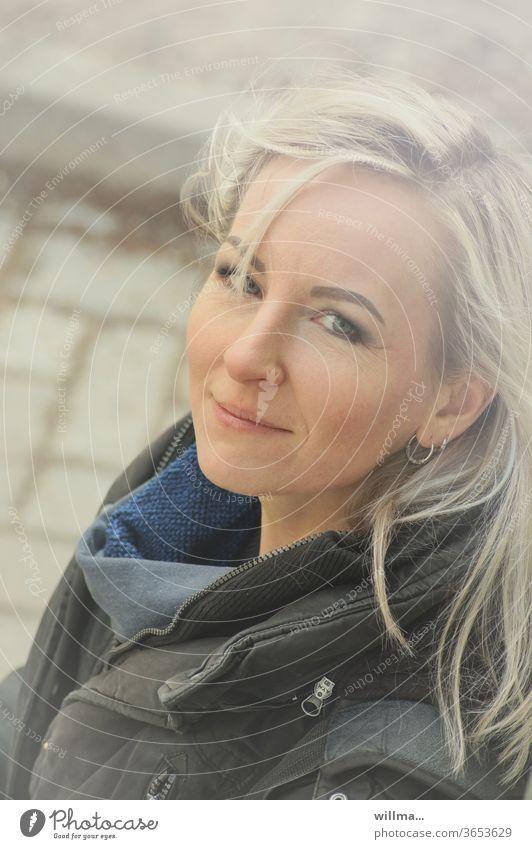 Porträt einer kessen Blondine Frau blond langhaarig schön lächeln blondiert feminin Ohrring Flirt nachdenklich freundlich abwartend Mensch Gesicht