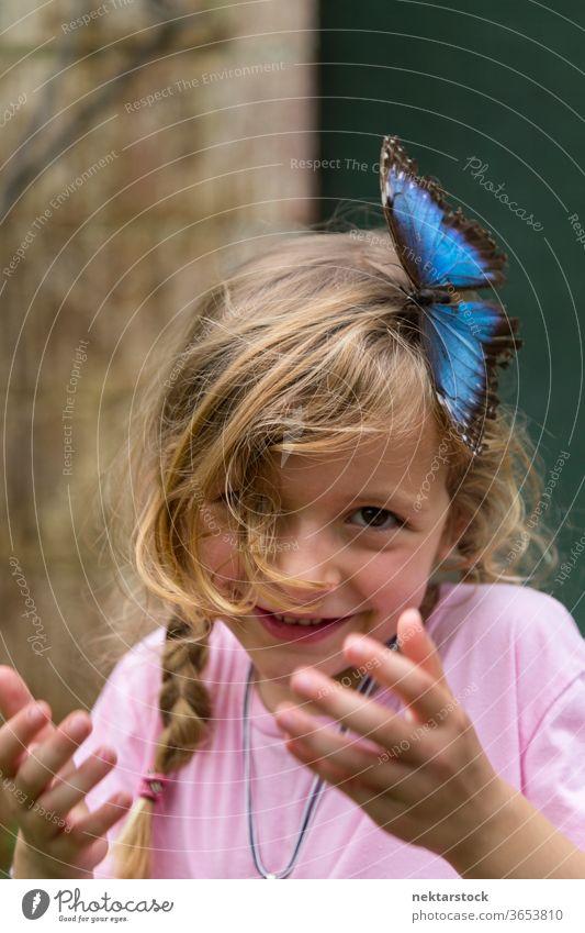 Porträt eines glücklichen blonden Mädchens mit blauem Schmetterling im Haar Kind Glück Lächeln im Freien Natur Schönheit in der Natur Tag Sommer