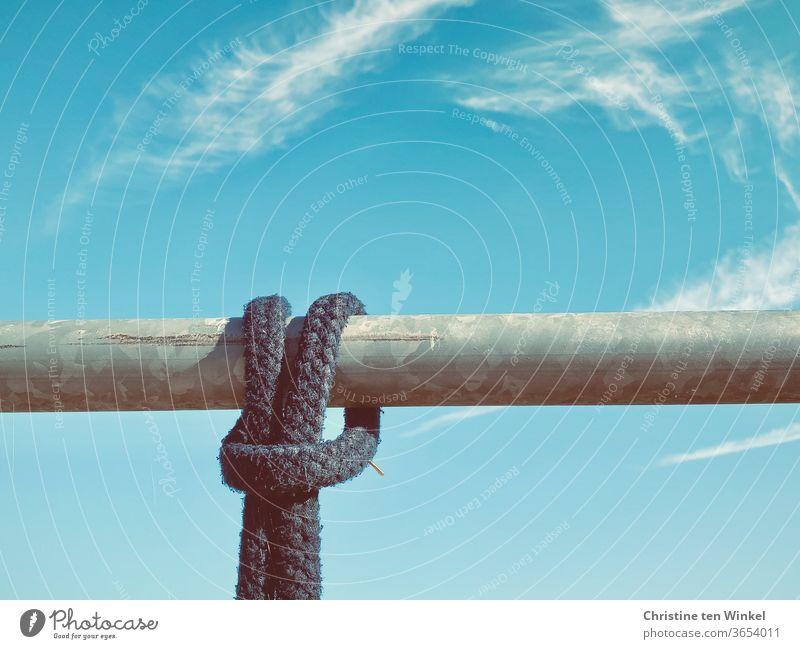 Ein dunkles Seil, festgebunden an einer waagerechten Metallstange. Nahaufnahme mit blauem Himmel und Wölkchen Tau Knoten Schnur Blauer Himmel Reiterhof