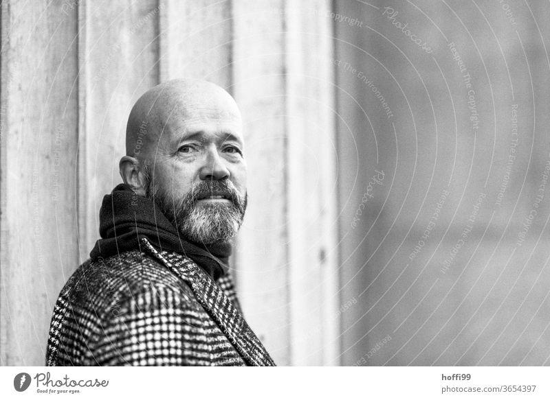 der Mann dreht sich zurück und schaut in die Kamera Bart Vollbart Mantel Glatzkopf Erwachsene maskulin Mensch Porträt 1 Blick in die Kamera Außenaufnahme