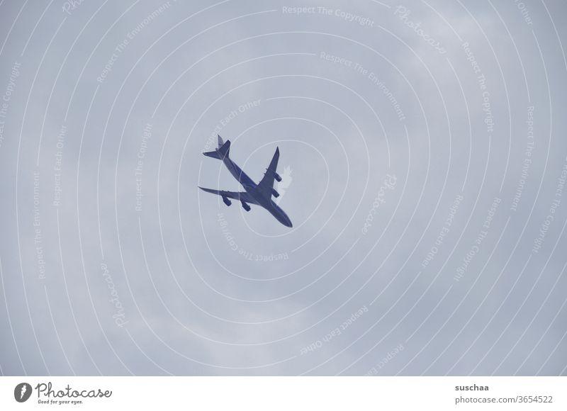 fliegendes flugzeug am wolkenverhangenen himmel Himmel Flugzeug Landeanflug Flughafen Anflug anfliegen Passagiere Urlaub Flugverbot Coronakrise Pandemie