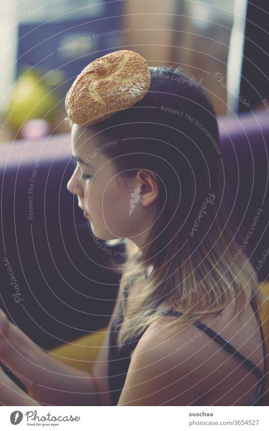 jugendliche mit einem brötchen auf dem kopf Mädchen Jugendliche Teenager seltsam skurril Hut Brötchen Kopfbedeckung Sesambrötchen Profil Haare Gesicht