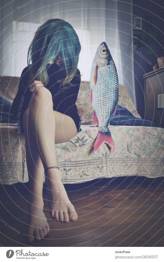 jugendliche mit perücke sitzt auf einem sofa neben einem fisch date mit fisch Füße Beine filmreif lustig Blick Jugend Idee Geschichte Story Perücke skurril