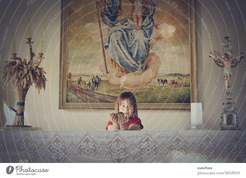 mädchen steht hinter einem altar in einer kapelle und hält einen apfel als gabe dar Chamansülz heilig Kindheit Kindererziehung Tischdecke Kreutz Gotteshaus