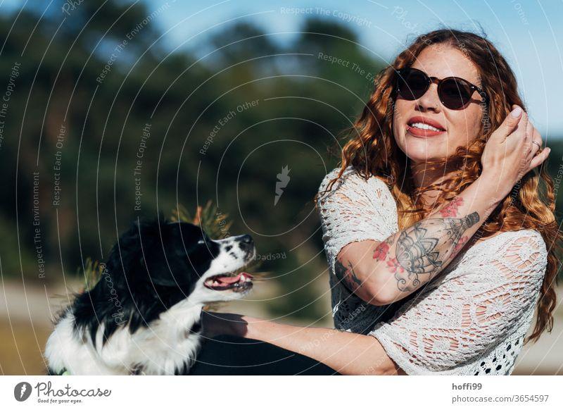 die junge Frau mit Sonnenbrille genießt die Sonne, Lana ihre Hündin will spielen ... rote Lippen Tätowierung Tatoo hübsch Jugendliche lockiges haar natürlich