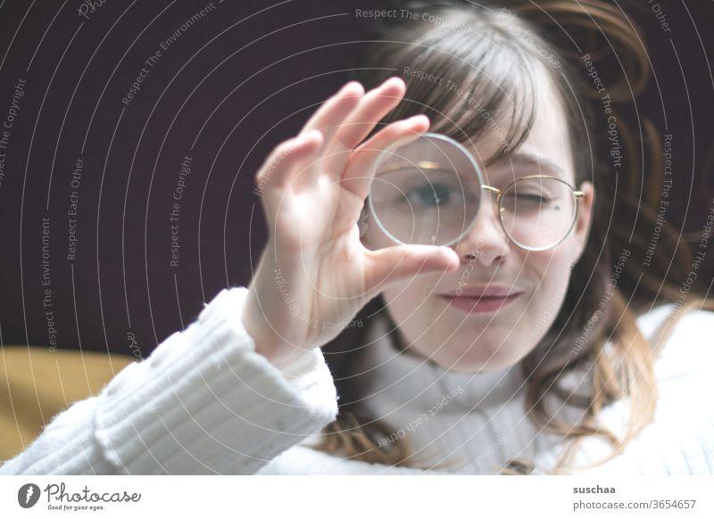 jugendliche, die sich ein vergrößerungsglas vor's auge hält Jugendliche Teenager Gesicht Brille Haare Auge Nase Mund lächeln gucken Vergrößerung Lupe
