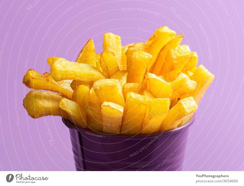 Pommes Frites in Nahaufnahme. Frittierte Lebensmittel. Pommes Frites auf violettem Hintergrund Amerikaner Kalorien Chips Cholesterin Knusprig Küche frittiert
