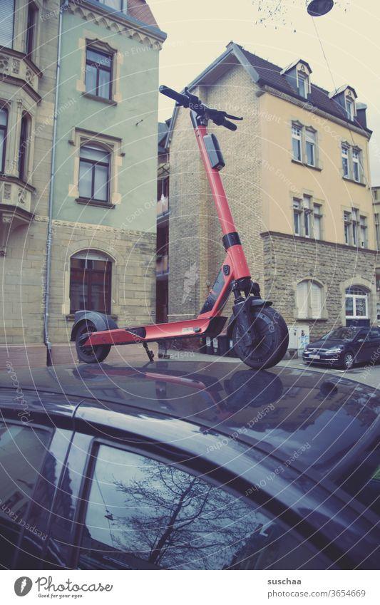 jemand hat einen e-roller auf einem auto geparkt E-Roller Auto Stadt Häuers Fenster Wohngegend urban Unfug Blödsinn grober Unfug Sachbeschädigung Streich