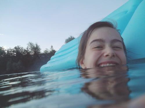 lachende jugendliche im seewasser mit luftmatratze Sommer See baden zu hause bleiben Urlaub zu Hause Seebad schwimmen nass Abkühlung Mädchen Teenager