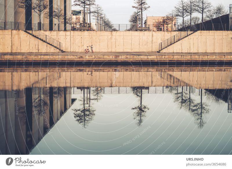 ein kleines Fahrrad steht einsam zwischen den Treppen am Spreebogen und betrachtet die Spiegelung der kahlen Bäume im Wasser Reflexion Ludwig-Erhard-Ufer Berlin