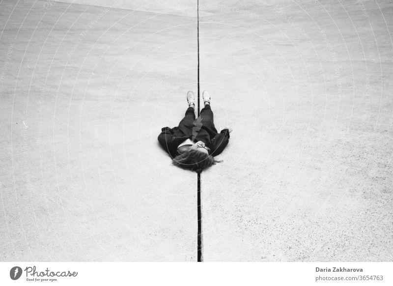 Genau in der Mitte von Nirgendwo Schwarzweißfoto Mädchen Frau Lügen vor Ort Frustration Erholung Depression verirrt tot erholend Kunst sich[Akk] entspannen