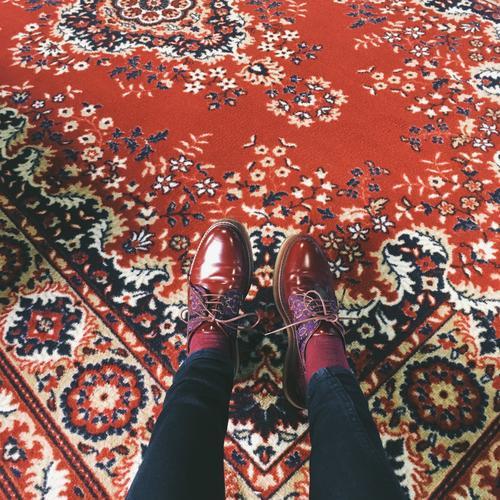 rote Schuhe auf rotem sowjetischen Teppich Perfekte Übereinstimmung Fuß Beine Bodenbelag Sowjet kastanienbraun Hose Frau Bekleidung feminin Jeanshose Farbfoto