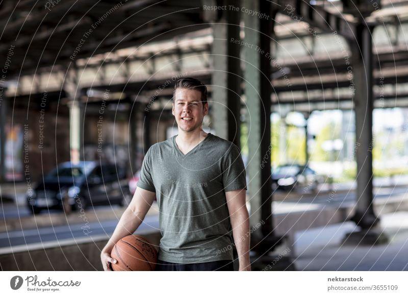 Mann mit Basketball unter Stadtbrücke stehend Erwachsener Kaukasier urban gutaussehend Model eine Person Frontseite in die Kamera schauen Straße Verkehr