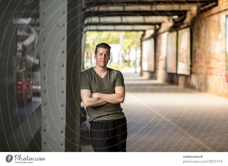Sportlicher Mann steht unter der Stadtbrücke Erwachsener Kaukasier urban gutaussehend Model eine Person Frontseite Sportkleidung Sportbekleidung Tag